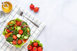 Vegetables on a white plate on a gray marble background. Top view. Salad made with cherry tomatoes, cucumbers, arugula, basil and dressed with olive oil. Healthy food concept, a vegan diet. Copy space