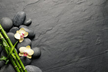 Spa Stones, Beautiful Orchid Flowers And Bamboo Stems On Black Table, Flat Lay. Space For Text