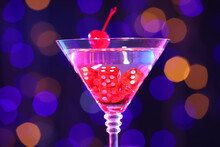 Cocktail With Casino Dice In Glass Against Blurred Lights, Closeup