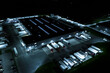 Aerial view of goods warehouse at Night. Logistics center in industrial city zone from above. Aerial view of trucks loading at logistic center. View from drone.