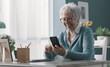 Leinwandbild Motiv Smiling senior lady using her smartphone