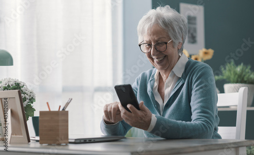 Smiling senior lady using her smartphone - fototapety na wymiar