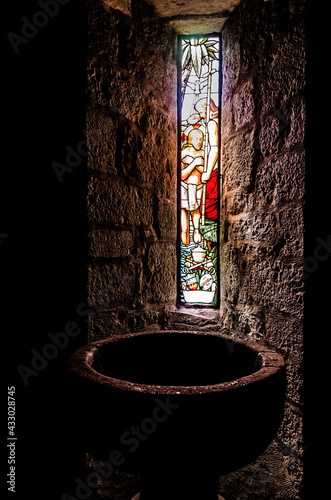 Fotografija Baptismal font in a medieval church illuminated by a stained glass window with b