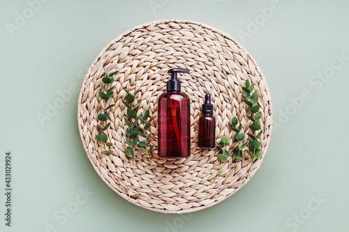 Obraz Dropper bottle of essential oil or serum, eucalyptus and dark dispenser bottle of shower gel. Beauty and SPA concept - fototapety do salonu