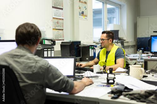 Obraz na plátně Büroarbeit - Mehrere Mitarbeiter arbeiten am Schreibtisch vor ihren PC's