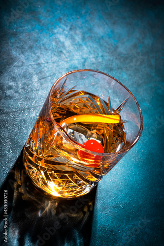 Old fashioned alcoholic cocktail with bourbon whiskey, marascino cherry and orange peel garnish, blue table, copy space, top view, hard light - fototapety na wymiar