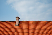 Red Tile Roof And Chimney Horizontally Towards The Blue Sky