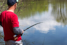 A Man Stands With A Fishing Rod On A Lake And Catches Fish On A Sunny Summer Day.
