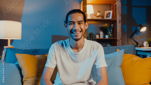 Fototapeta Happy young freelance asian man looking at camera smile and talk with friends on video call online at night in living room at home, Stay at home quarantine, work from home, Social distancing concept. obraz