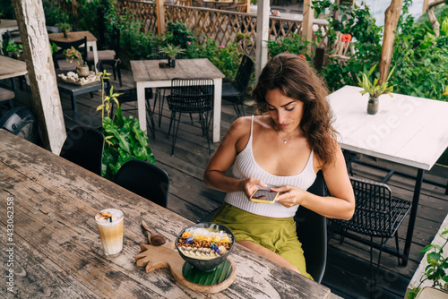 Fototapeta Concentrated woman texting on smartphone in cafe obraz