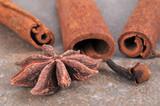 Fototapeta Kawa jest smaczna - Bâtons de cannelle et des clous de girofle avec de l'anis étoilé en gros plan sur fond gris