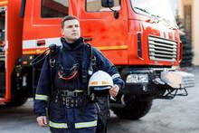 Portrait Of Caucasian Firefighter In Uniform And Helmet Near Fire Engine.