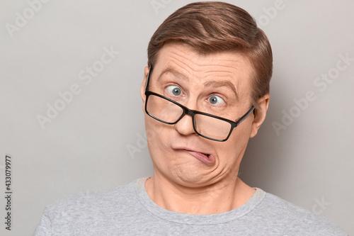 Fotografie, Obraz Portrait of funny weird mature man making goofy crazy face
