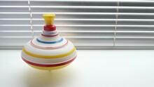 Spinning Whirligig, Child Toy On Background Of Blinds.