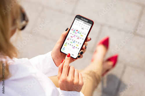 Fototapeta Woman schedule her time by using calendar app on mobile phone obraz
