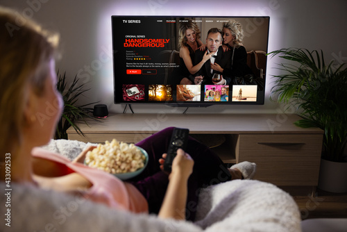 Woman watching TV series and movies via streaming service at home - fototapety na wymiar