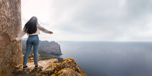 Panoramic View Of A Young Woman Standing On A Cliff In Front Of The Sea