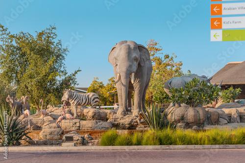 Naklejka premium 23 February 2021, Dubai, UAE: Zebra, elephant and crocodile statues on an artificial fountain and waterfall in the central safari village at Dubai Zoo