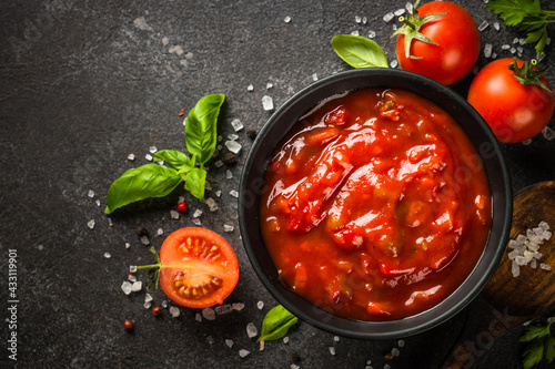 Fototapeta Tomato sauce in a bowl with spices, herbs and fresh tomatoes. Top view with copy space. obraz