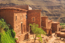 View On Empty Village With Steep Dirt Path Into Dry Arid Valley With Sparse Vegetation Beyond Traditional Berber Clay Stone Houses, Rugged Rock Face Background - Morocco, High Atlas Mountains