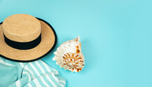 Straw Hat, Sea Shell, Towel On A Blue Background.