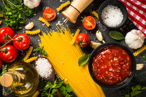 Fototapeta Italian food background. Pasta, olive oil, tomato sauce, spices, basil and fresh tomatoes. Top view with copy space. obraz