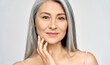 Closeup portrait of gorgeous happy middle aged mature asian woman, senior older 50 year lady looking at camera touching her face isolated on white. Ads of lifting anti wrinkle skin care treatment.