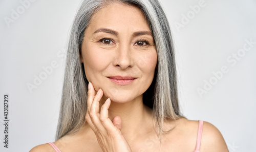 Photo Closeup portrait of gorgeous happy middle aged mature asian woman, senior older 50 year lady looking at camera touching her face isolated on white