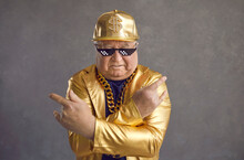 Retired Older Adult Man In Thug Life Glasses, Gold Chain And Disco Outfit Isolated On Gray Background. Studio Portrait Senior Pensioner In Funny Sunglasses Looking At Camera With Angry Face Expression