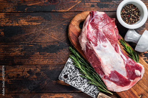 Fotografie, Obraz Raw lamb mutton shoulder meat on the bone on a wooden butcher cutting board with cleaver