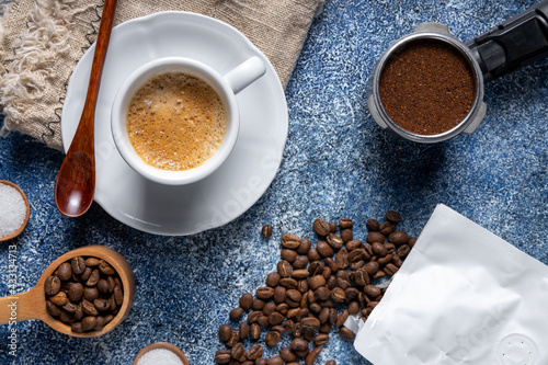 Obraz Top view of a cup of coffee, a coffee container and a pile of coffee on the kitchen table - fototapety do salonu