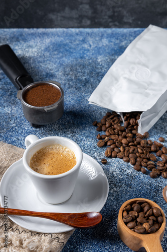 Obraz Vertical shot of a cup of coffee, a coffee container and a pile of coffee on the kitchen tab - fototapety do salonu