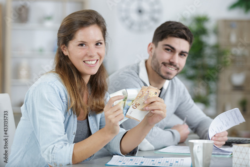 two workers are holding money - fototapety na wymiar