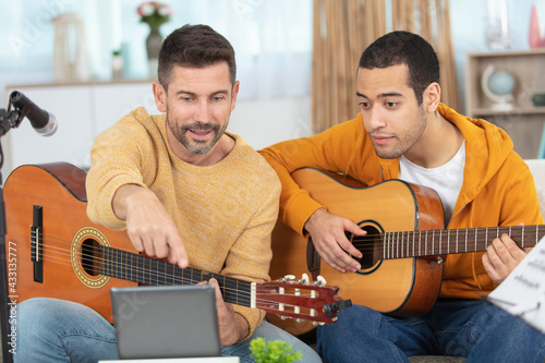 young man learning to play the guitar with teacher - fototapety na wymiar