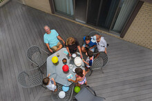 Aerial View Of Family And Grandparents Celebrating A Birthday Party Outdoors On Patio