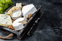Assorted Cheese Platter With Brie, Camembert, Roquefort, Parmesan, Blue Cream Cheese, Grape And Nuts. Black Background. Top View. Copy Space