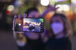 Cheerful Caucasian female friends with masks taking photos at an amusement park in the evening