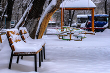 Benches In The Yard Under The Snow. In The Background In Blur Sandbox, Carousel, Cars. Winter Landscape.