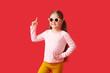 Leinwandbild Motiv Cute little girl wearing stylish sunglasses and pointing at something on color background