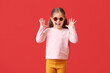 Leinwandbild Motiv Cute little girl wearing stylish sunglasses on color background