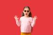 Leinwandbild Motiv Surprised little girl wearing stylish sunglasses on color background