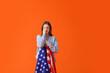 Leinwandbild Motiv Sad young woman with USA flag on color background. Memorial Day celebration