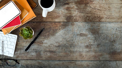 Obraz Mock up smart phone over notebook, keyboard, coffee cup and copy space on wooden background. - fototapety do salonu