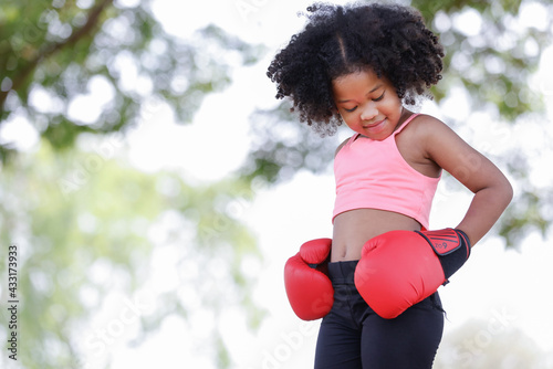 childhood and people concept - little african american curly hair girl wear gym clothes and red boxing gloves,looking down beautiful shape. - fototapety na wymiar