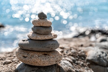 Tower Of Stones. Balanced Pebble Pyramid On The Beach On A Sunny Day. Blue Sea On The Background. Selective Focus, Bokeh. Zen Stones On The Sea Beach, Meditation, Spa, Harmony, Tranquility, Balance