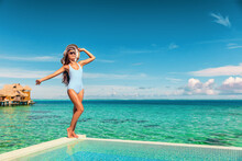 Travel Vacation Tourist Woman Relaxing At Infinity Pool In French Polynesia. Happy Woman In Swimsuit And Sun Hat Over Blue Ocean At Luxury Resort. Elegant Lady Enjoying Holiday Lifestyle.