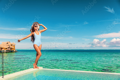 Fototapeta Travel vacation tourist woman relaxing at infinity pool in French Polynesia. Happy woman in swimsuit and sun hat over blue ocean at luxury resort. Elegant lady enjoying holiday lifestyle. obraz