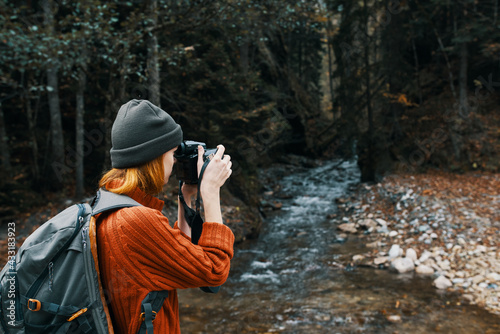 woman with a camera on nature in the mountains near the river side view - fototapety na wymiar
