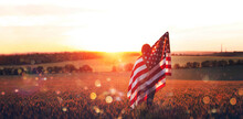 Independence Day. Beautiful Young Woman With The American Flag In A Wheat Field At Sunset With Bokeh And Sparkle. 4th Of July.