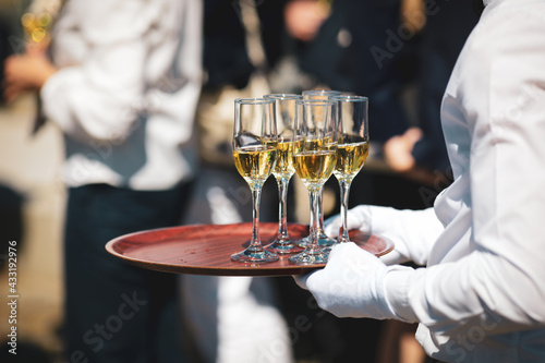 Canvastavla Shallow depth of field (selective focus) details with a waiter walking around and giving sparkling wine to the guests of an event